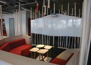 Los espacios de reunión con pantallas de proyección de corta distancia invitan a los empleados del banco y a los invitados a sentarse y colaborar
