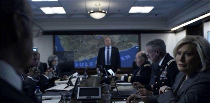 """Justo enfrente del Presidente, al igual que en la verdadera Sala de Situación de la Casa Blanca, se encuentra un Touch Panel AMX Modero de 7"""" que el Presidente puede utilizar para controlar los micrófonos de la sala y otros medios AV. Imagen cortesía de Netflix."""